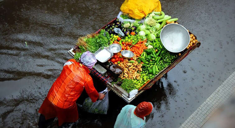 Foto of poeple walking with colourful vegetables on a tow truck through a flooded street