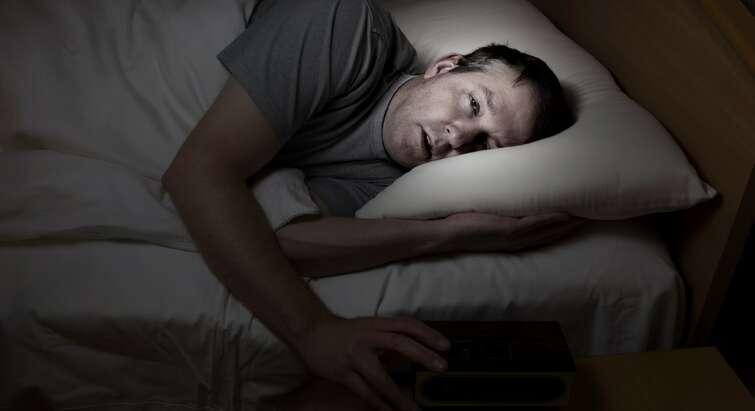 Mand prøver at falde i søvn