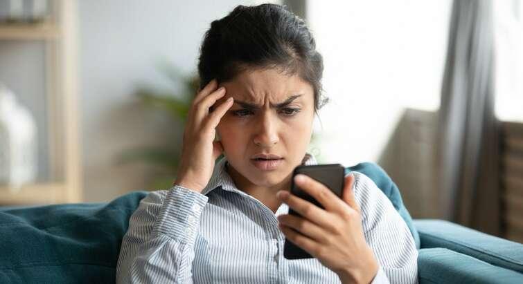 Foto af en kvinde, der kigger frustreret på sin mobil