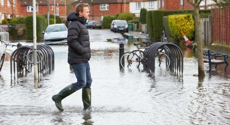Regnfyldt gade med gående mand