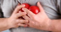 Person holder rødt hjerte uden på tøjet